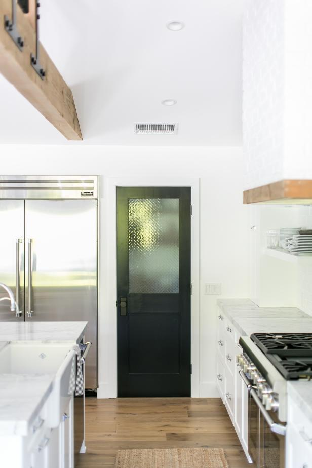 Black Pantry Door In Bright White Kitchen With White