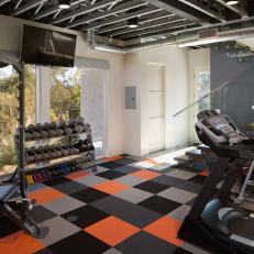 Home Gym With Black, Gray and Orange Square Carpet, Glass Lined Staircase and Exercise Machines