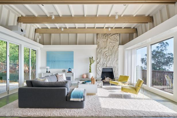 Large windows and glass doors fill the living room with lots of natural lighting. A plush, gray sectional and a pair of cheery yellow armchairs offer comfortable and stylish seating.