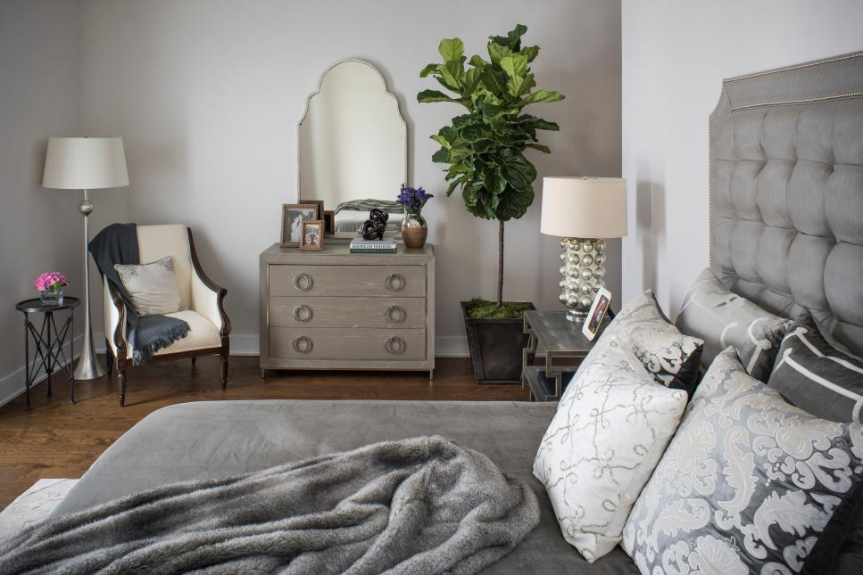 Gray Bedroom With Neutral Armchair and Brown Dresser and Mirror