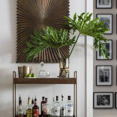Dining Room With Brass Bar Cart And Modern Wooden Wall Sculpture