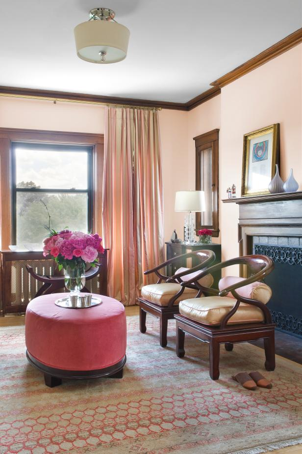 Peach Living Room With Vibrant Pink Ottoman and Flowers