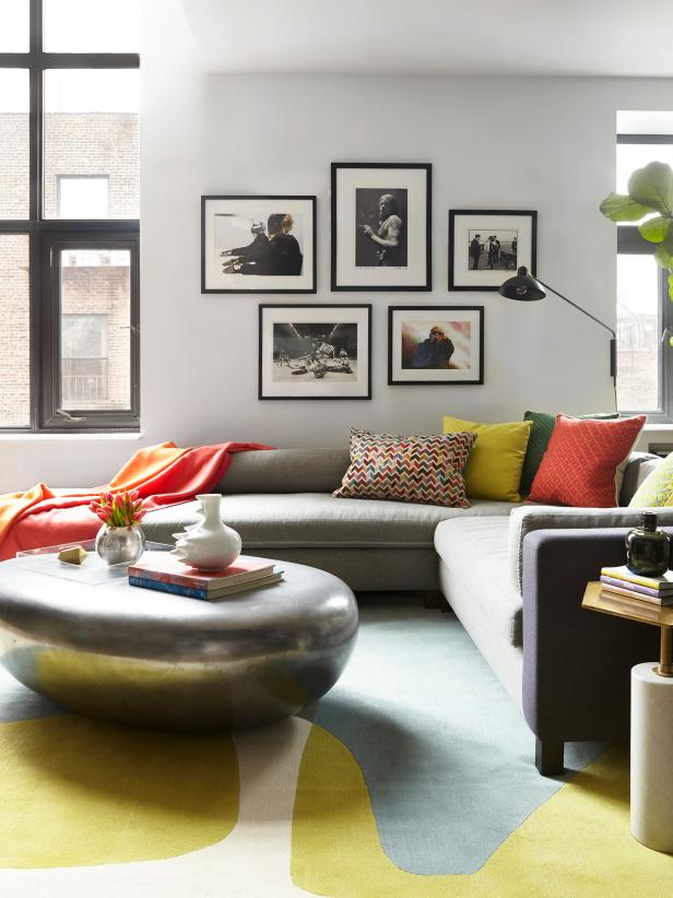 Brightly colored pillows and a rug give a vibrant splash of color to the living room, where silver and gray are the backdrop neutrals. The soft curved shapes of both the sectional and ottoman are family-friendly yet totally sophisticated choices.