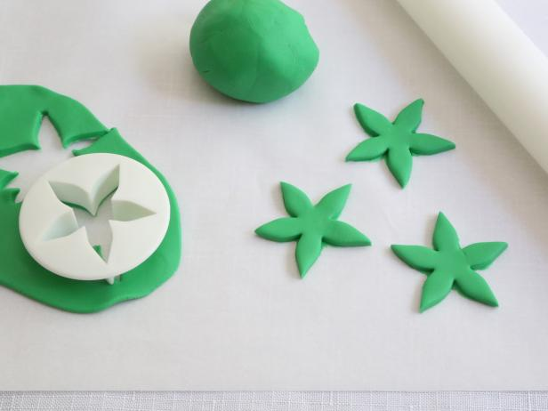 Roll the green ready-made fondant to 1/4-inch thickness with a rolling pin and cut out flower shapes using a fondant cutter. You can also cut a free-hand a flower shape from the fondant using a small knife.