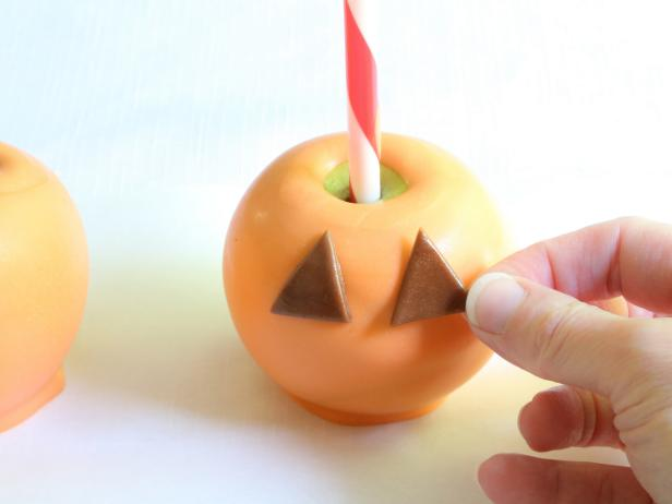 Lightly brush the backs of the pieces with corn syrup and arrange the pieces onto the apples so that a jack-o-lantern face is achieved.