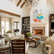 Open, Tall Ceiling With Wood Beams, Shiplap Accent Wall Over the Fireplace and Soft Green Sofas