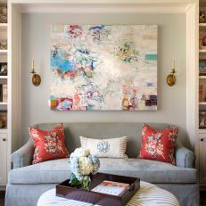 Bookshelf Framed Sitting Space With Pastel Blue Sofa, Bright Coral Throw Pillows and Upholstered Striped Ottoman