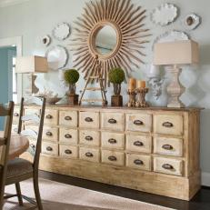 Plate Wall and Tabletop Display Featuring Rectangular Shaded Table Lamps Over Distressed Buffet With Drawer Storage