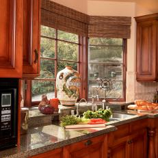 Warm Wood Upper And Lower Kitchen Cabinetry With Neutral Granite Countertop  Sink Bay Windows
