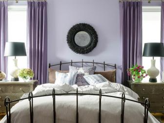Transitional Lavender Bedroom With Wrought Iron Bed, Striped Comforter and Purple Curtains