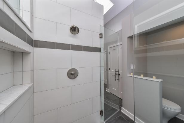 White Subway Tile Shower With Gray Accent Strip and Glass Door
