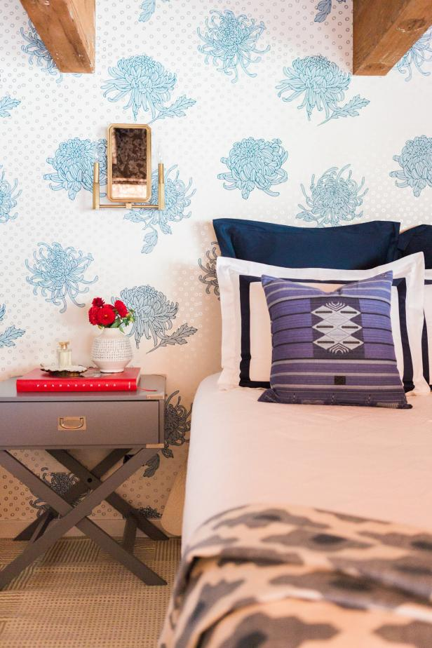 Bedroom With Blue Floral Wallpaper and Red Accents