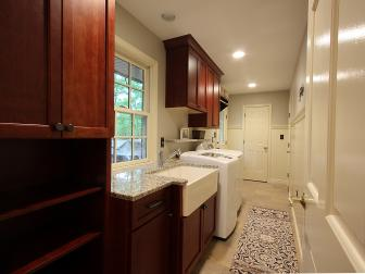 Spacious Laundry Room With Cherry Wood Cabinets and Farmhouse Sink