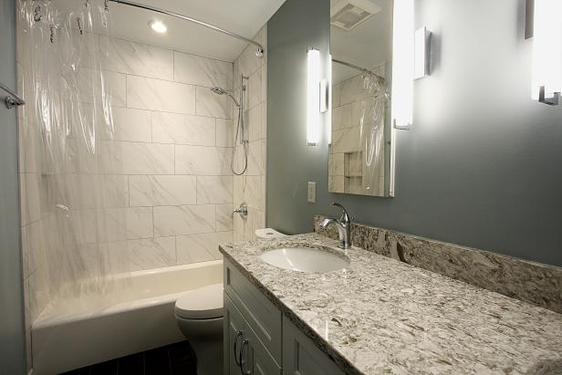 Gray Bathroom With Porcelain Tile and Sconce Lights