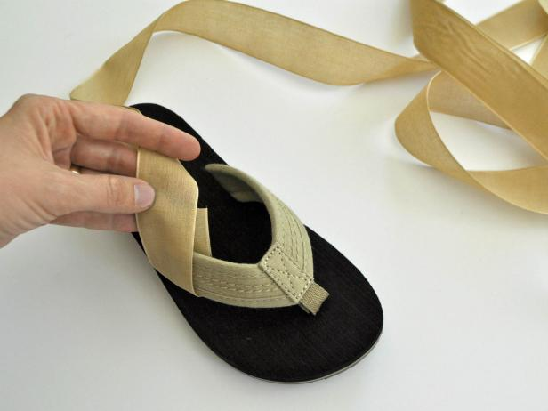Cut spool of ribbon into four equal parts. Wrap ribbon around flip flop strap and glue as shown. Repeat on other side of flip flop so there are two straps on each sandal. Repeat on other flip flop. Lace shoes up the leg. Tie in a knot and tuck in edges of ribbon.
