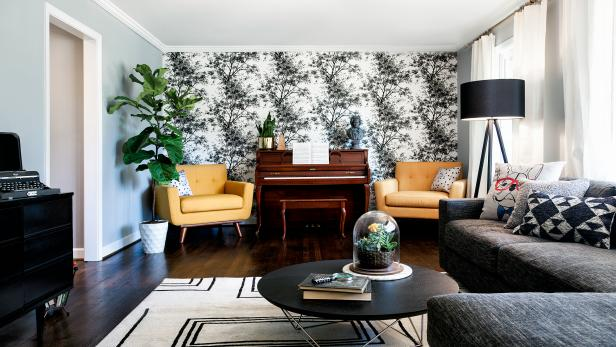 This lively living room features two bold yellow midcentury modern chairs positioned on either side of a traditional piano. Black and white floral wallpaper provides a backdrop, while potted plants add a touch of natural decor. The cozy gray sectional provides a cozy spot to relax.