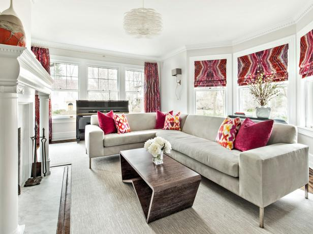 Bring texture, color and pattern to the  living room with eye-catching window treatments. Here, bold hues from the window treatments are repeated in the throw pillows to inject color into the sleek, gray sectional. A large fireplace with classic moldings acts as the focal point of the room.