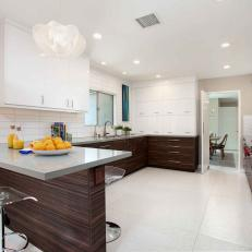 Bright White Midcentury Modern Kitchen With Woodgrain And White Cabinets  And Built In Eat In Bar Space