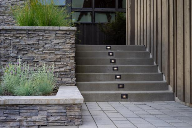 Concrete Outdoor Stairs and Stacked Stone Retaining Walls With Shrubs