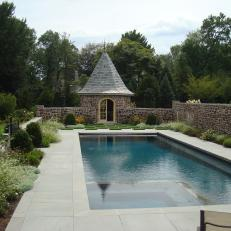 Quaint Cottage Backyard Swimming Pool With Surrounding Stone Wall, Planted Border and Small Covered Shed