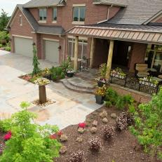Grand Front Entrance Featuring Neutral Tone Walkway, Covered Front Porch and Vibrant Plant Life