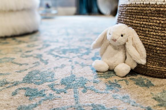 Nursery With Neutral and Blue Floral Rug and Stuffed Bunny