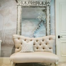Chic Baby Boy's Nursery With Neutral Tufted Chair and Vintage Mirror