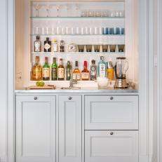 Well-Stocked Wet Bar With Glass Shelves and White Cabinets