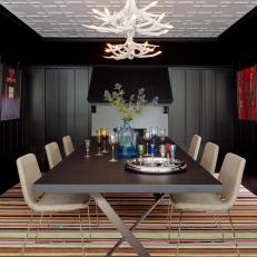 Black Dining Room With Striped Rug and Antler Chandeliers