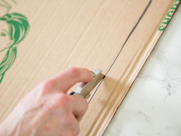 Step 4-  Measure, Score & Cut BaseWith your 10-inch width in mind, add four more inches which will allow for a two-inch lip on either side and cut out. Then, with the bottom side up, lightly score the cardboard with a utility blade lightly score along the sides for easy folding.