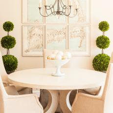 White Dining Room With Round Table and Triple-Ball Topiaries