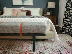 Add a high-end touch to your bedroom on a budget. Learn how to upcycle an inexpensive coffee table into a luxe upholstered bench with leather strap details.