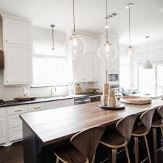 White Farmhouse Kitchen With Island and Midcentury Stools