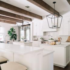 White Kitchen With Ceiling Beams, Two Islands and Eat-In Bar