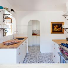 White Cottage Kitchen With Gas Range and Arched Door