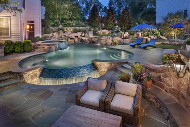 stone patio with infinity pool  waterfall and fireplace