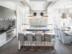 White Modern Farmhouse Kitchen with Dual Waterfall Quartz Islands, Steel Vent Hood, Bar Stools, Custom Tables, Porcelain Tile Backsplash, Banquette and Stainless Steel Appliances