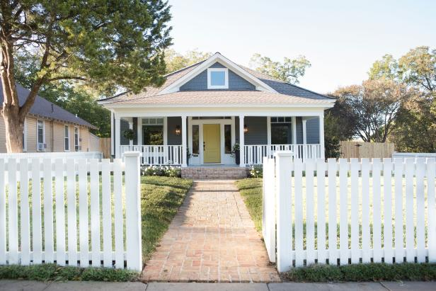 Blue Home Exterior with Yellow Door and White Picket Fence