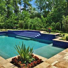 Blue and Turquoise Swimming Pool With Corner Garden