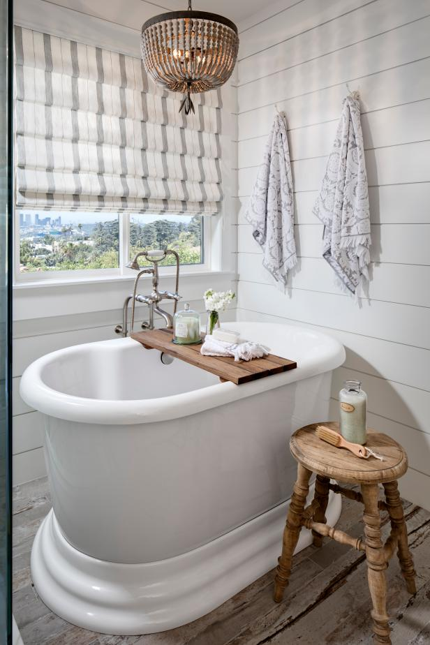 A coastal master bathroom that features a white oval freestanding tub.