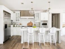 Contemporary White Kitchen With Island Seating And Modern Pendants And Appliances