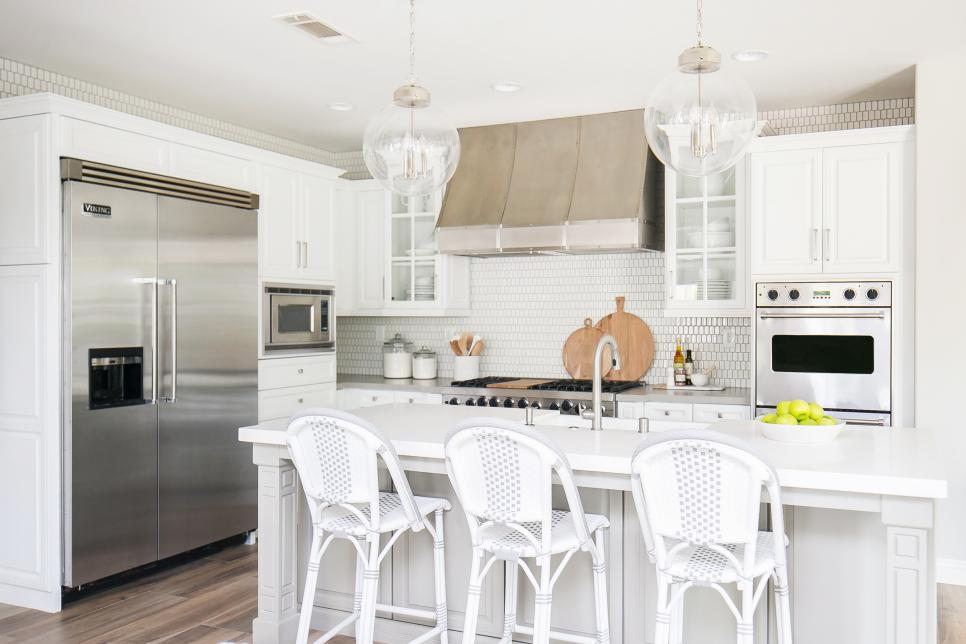 Contemporary White Kitchen With Island Seating And Modern Pendants