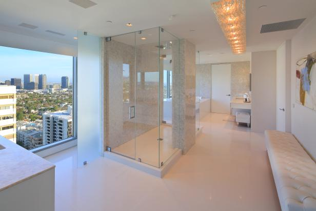 A large master bathroom with modern finishes and views of the city.