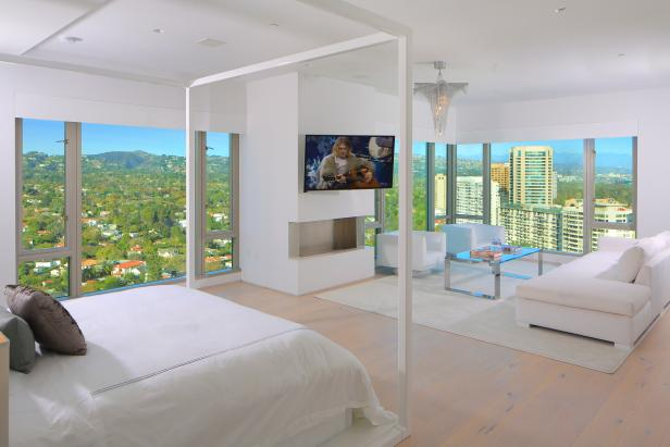 A modern penthouse master bedroom with high glamour and views.