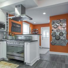 Modern White Kitchen With Orange Accent Wall Color and Custom Pot Hanging Rack