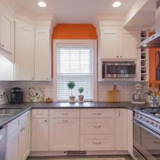 White Subway Tile Kitchen With Reclaimed Wood Cabinetry and Orange Accent Wall
