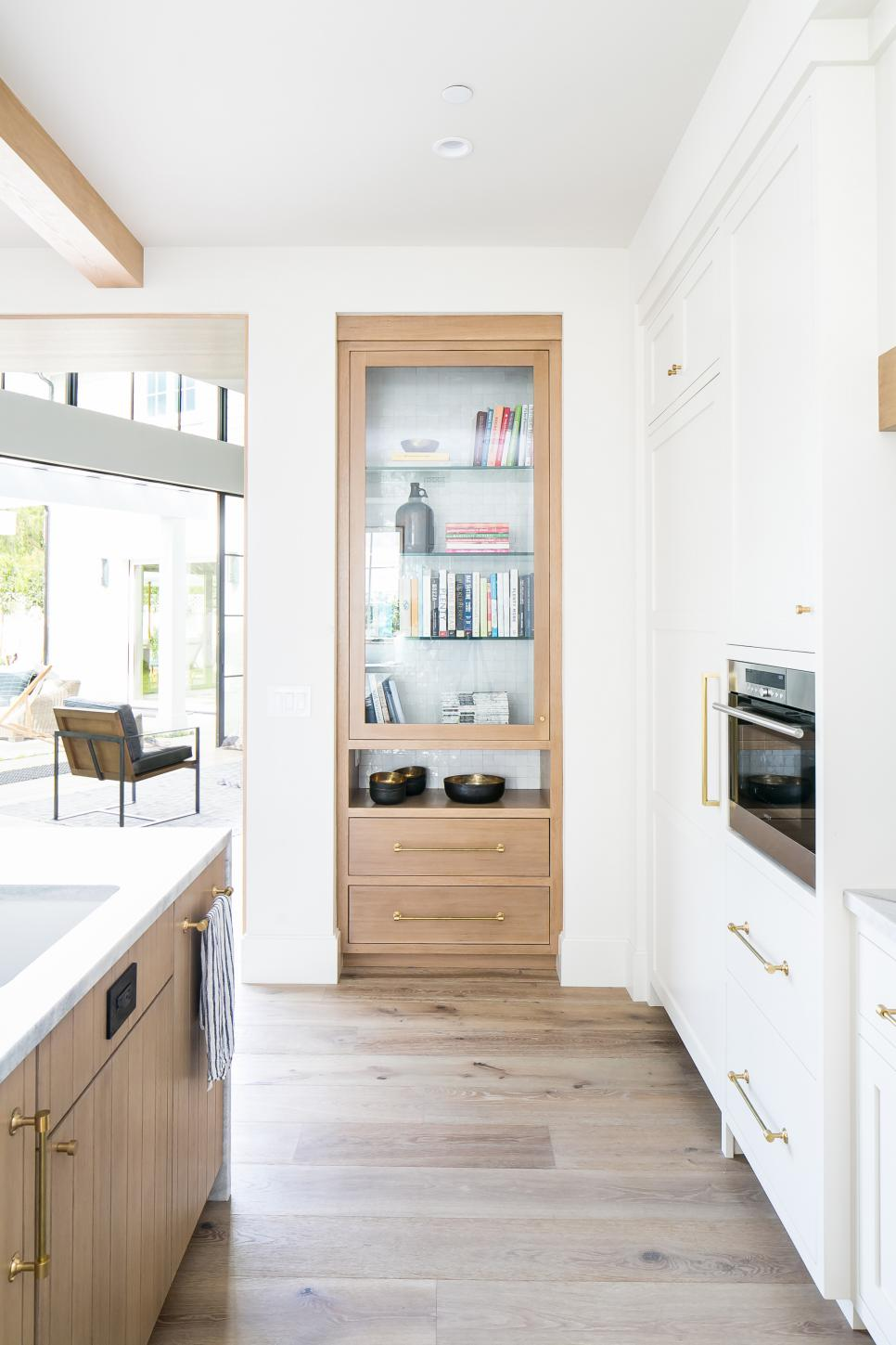 eclectic white kitchen with wood bookshelf