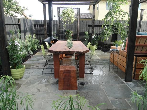 Table With Living Plants on Patio With Gray Fence and Bamboo Plants