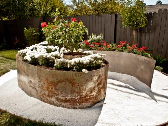 Fenced Backyard With Oversized Metal Planters in White Gravel