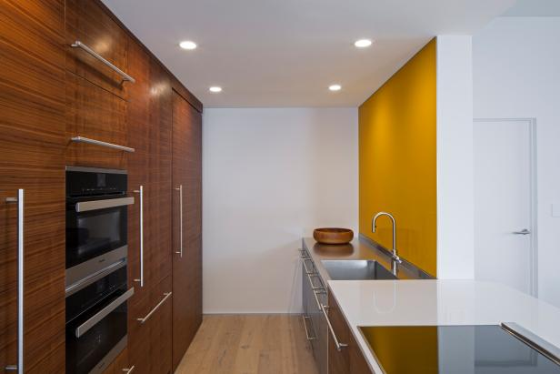 Modern Galley Kitchen With Yellow Glass Accent Wall